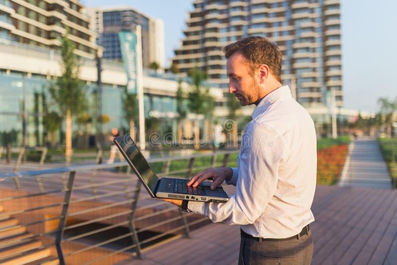 Бизнесмен используя ноутбук перед офисным зданием стоковое фото
