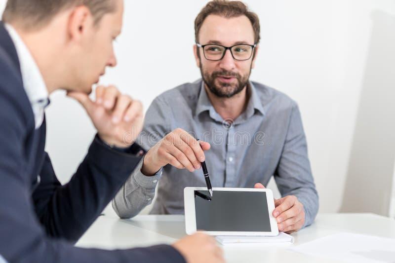 Бизнесмен 2 используя прибор планшета пустого экрана пока сидящ на столе на встрече стоковые изображения rf