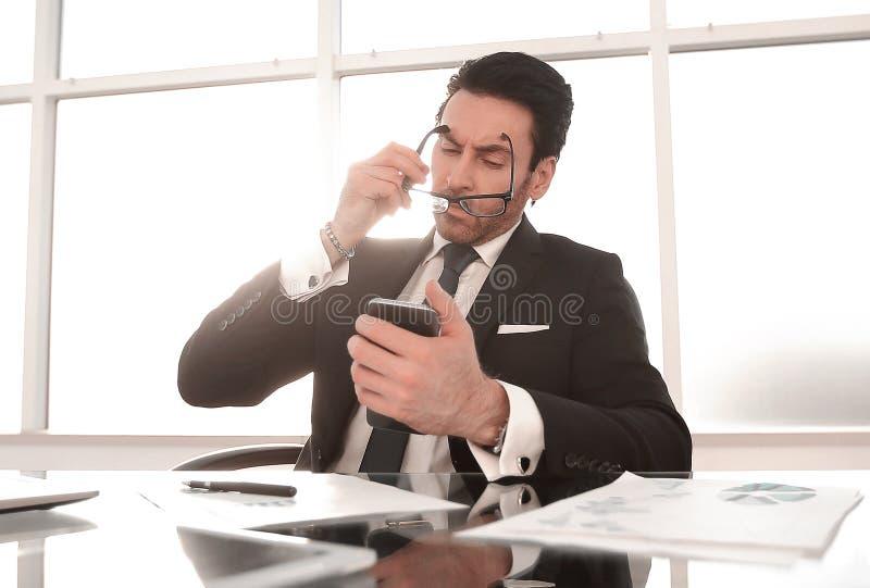 Бизнесмен используя смартфон сидя на его столе стоковая фотография