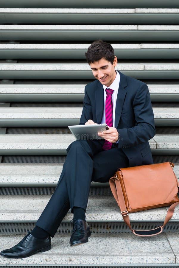 Бизнесмен используя таблетку для сообщения или хранения данных вне стоковые фотографии rf