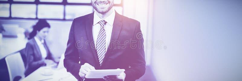 Бизнесмен используя цифровую таблетку пока коллега в предпосылке стоковая фотография