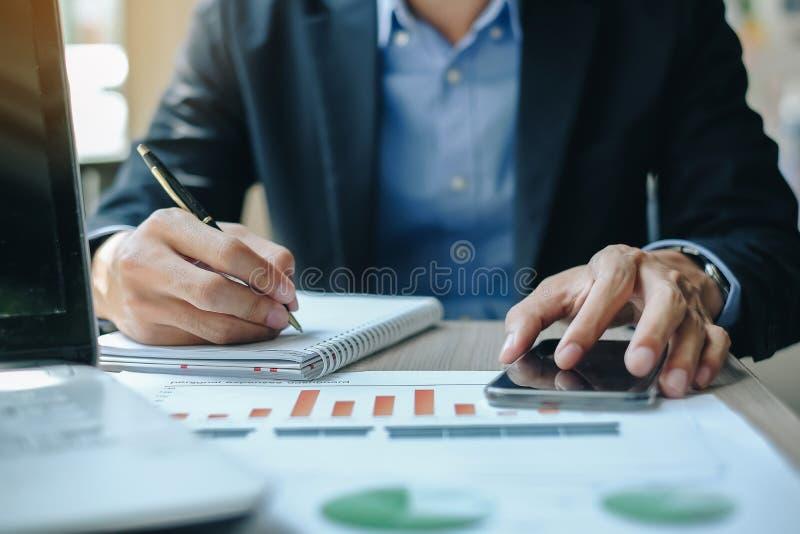Бизнесмен используя smatphone для плана анализа maketing стоковое изображение rf