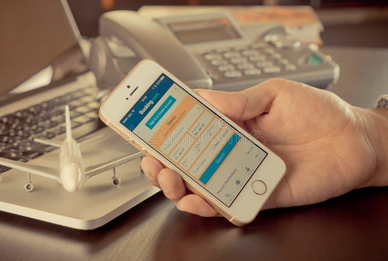 Бизнесмен использует мобильный телефон для того чтобы записать гостиницу на резервировании com стоковая фотография rf
