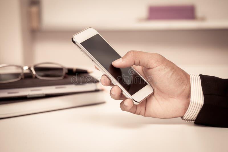 Бизнесмен использует умный телефон, таблетку, мобильный телефон в офисе стоковое изображение rf
