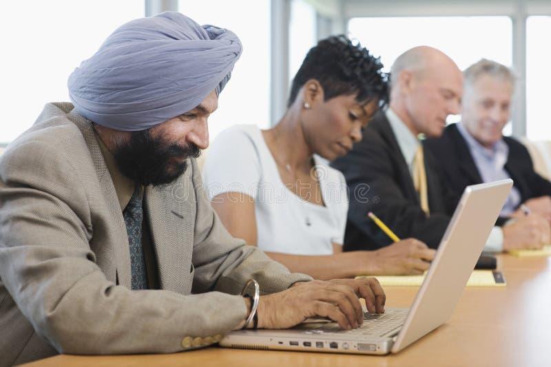 Бизнесмен используя компьтер-книжку кроме многонациональных коллег стоковая фотография