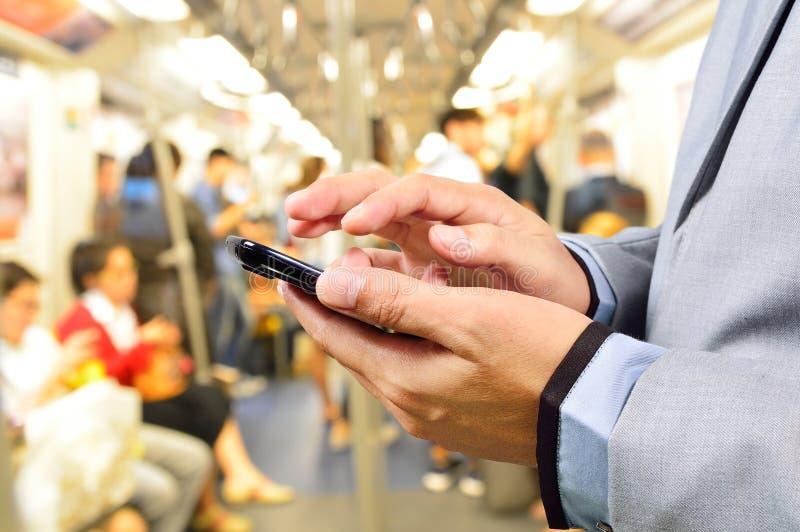 Бизнесмен используя мобильный телефон в поезде стоковая фотография