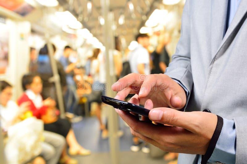 Бизнесмен используя мобильный телефон в поезде стоковое изображение rf