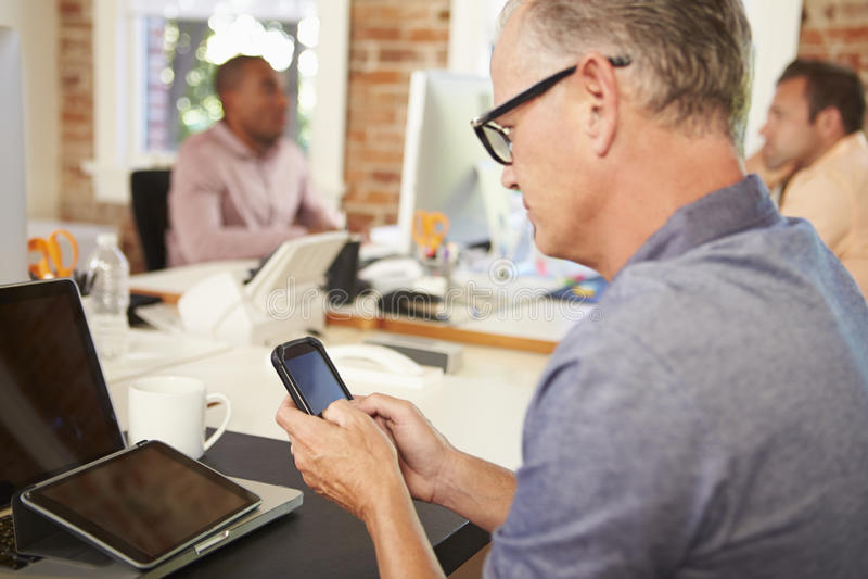 Бизнесмен используя мобильный телефон в творческом офисе стоковое фото rf
