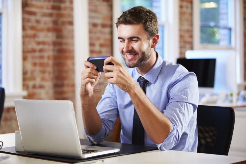 Бизнесмен используя мобильный телефон в творческом офисе стоковые изображения rf