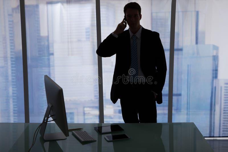 Бизнесмен используя сотовый телефон на столе стоковое изображение rf