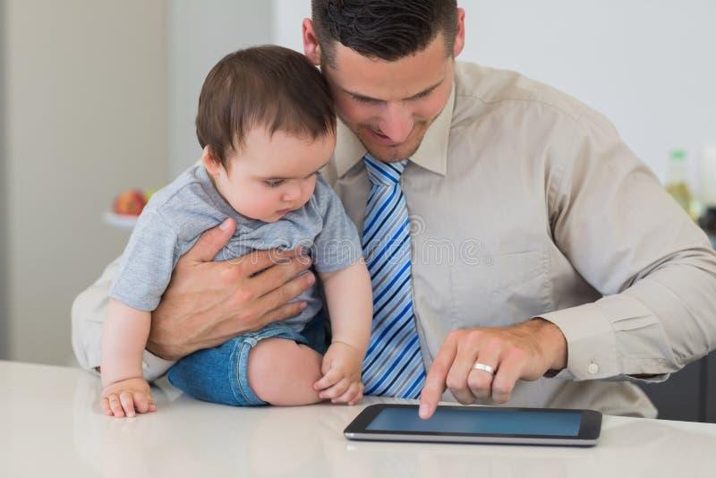 Бизнесмен используя таблетку пока держащ младенца стоковое фото
