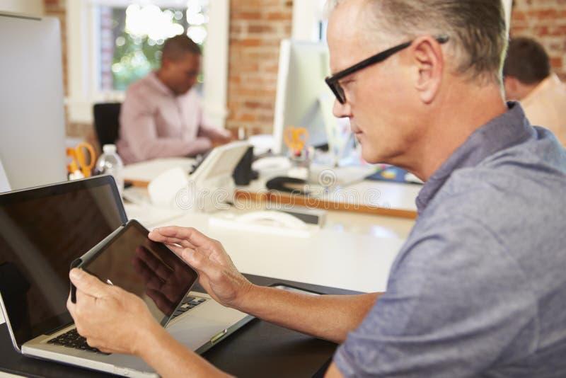 Бизнесмен используя таблетку цифров в творческом офисе стоковое фото rf