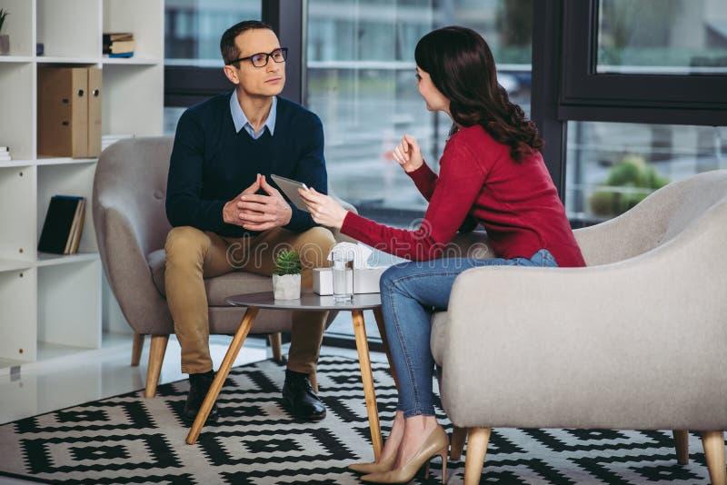 Бизнесмен и коммерсантка говоря совместно стоковое изображение
