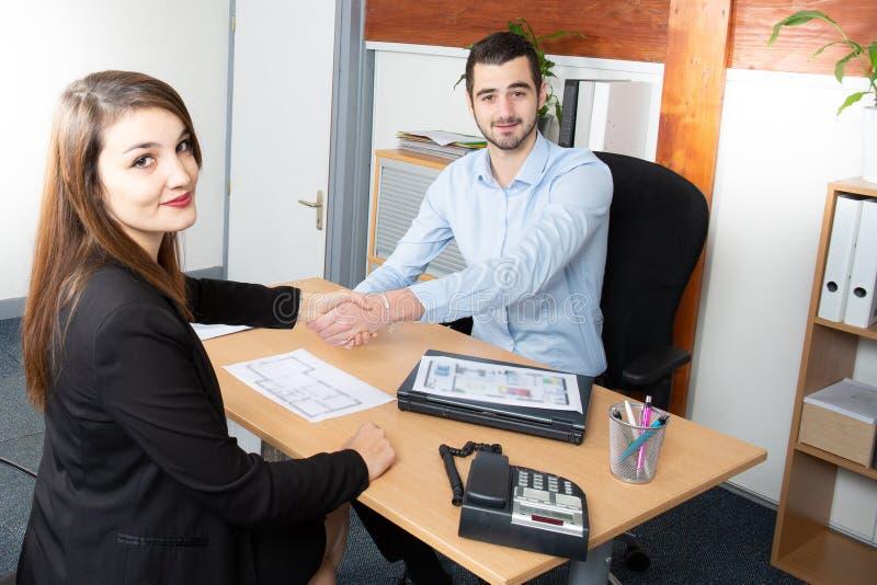 Бизнесмен и коммерсантка тряся руки в столе офиса после контракта стоковое фото rf