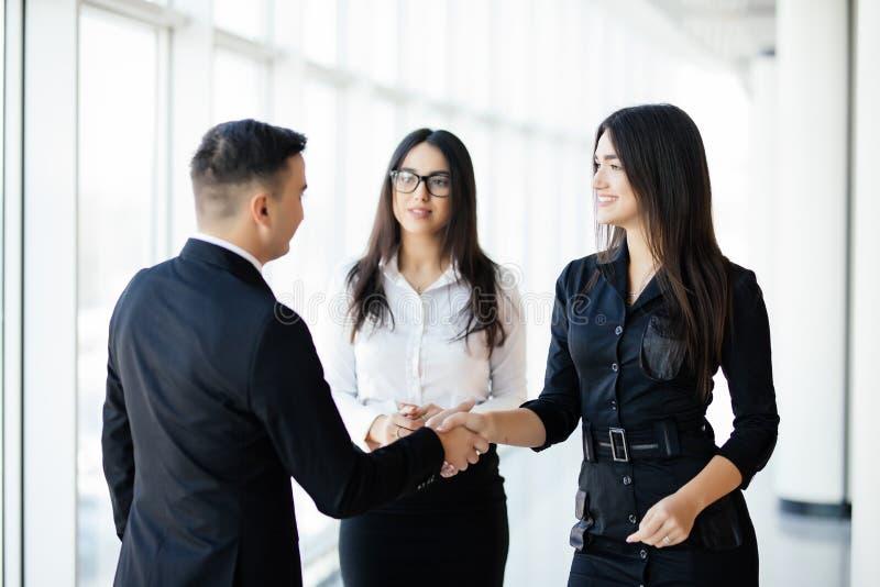 Бизнесмен и коммерсантка тряся руки в ярком офисе стоковая фотография rf