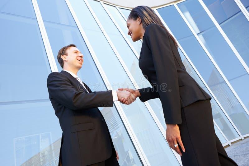 Бизнесмен и коммерсантки тряся руки стоковые изображения rf