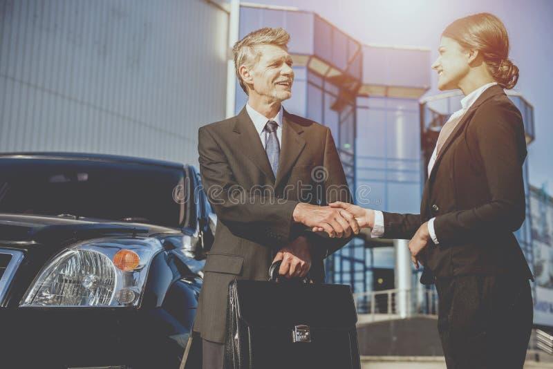 Бизнесмен и молодая коммерсантка тряся руки стоковая фотография