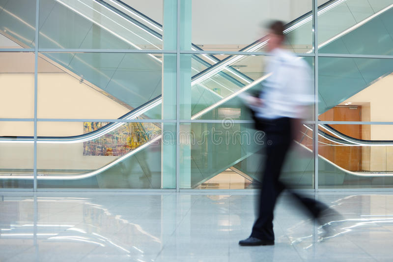 Бизнесмен идя быстро вниз с Hall в офисном здании стоковое изображение rf