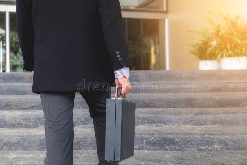 Бизнесмен идя вверх по лестницам и держа портфель в Хане стоковые изображения rf
