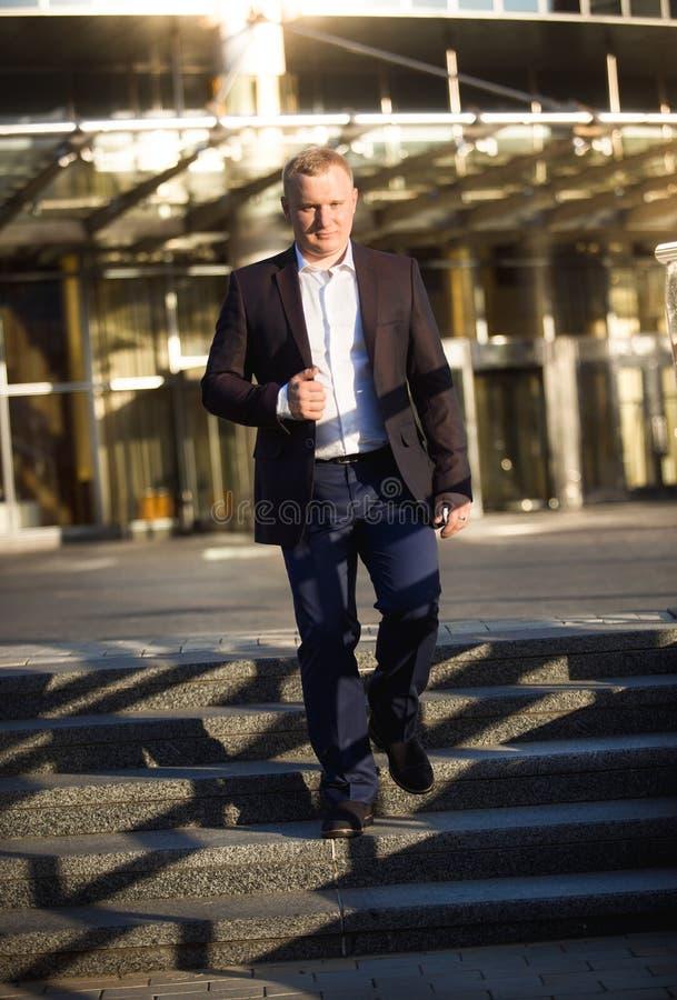 Бизнесмен идя вниз с каменных лестниц на деловом центре стоковое изображение rf