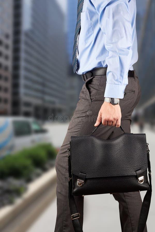 Бизнесмен идя и держа кожаный портфель в его Хане стоковые фото