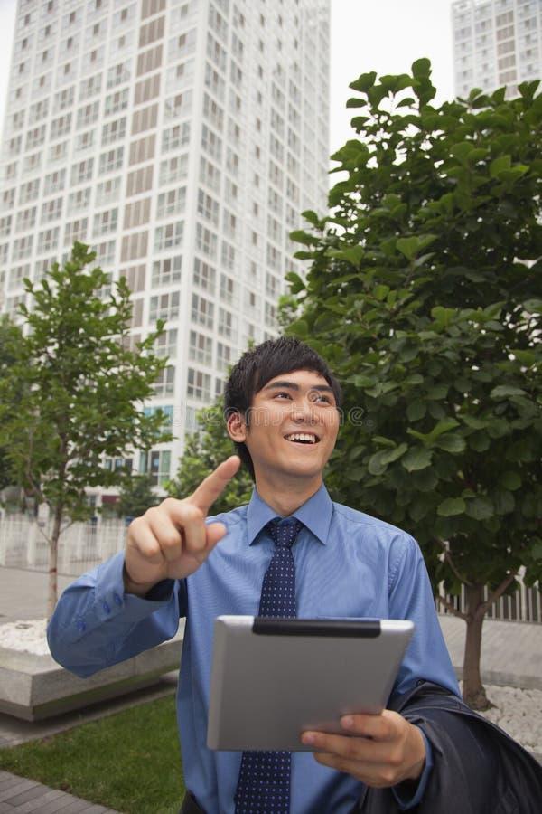 Бизнесмен идя outdoors с его цифровой таблеткой стоковое фото