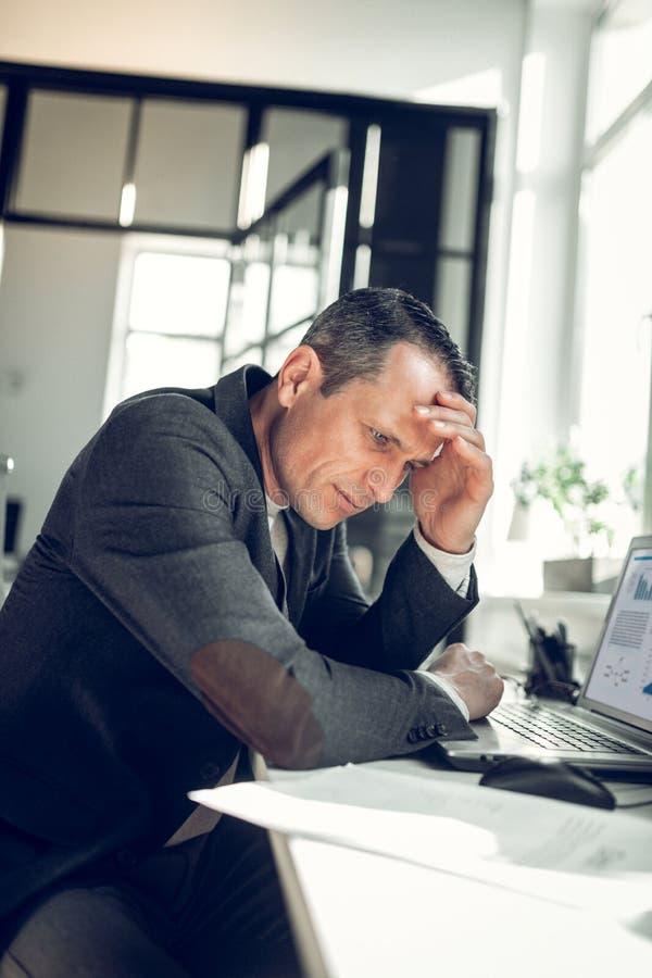 Бизнесмен касаясь его голове пока чувствующ занятый работы стоковые фотографии rf