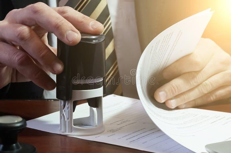 Бизнесмен кладет штемпель на контракт стоковое фото rf