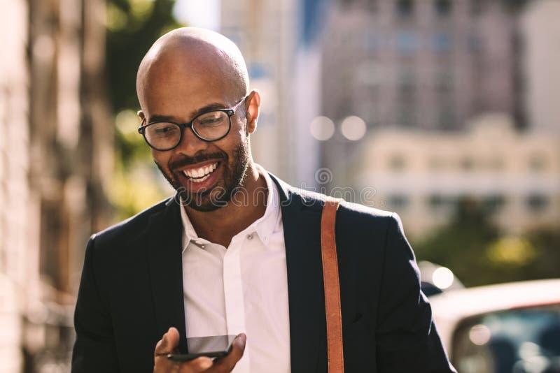 Бизнесмен коммутируя с мобильным телефоном outdoors стоковые изображения