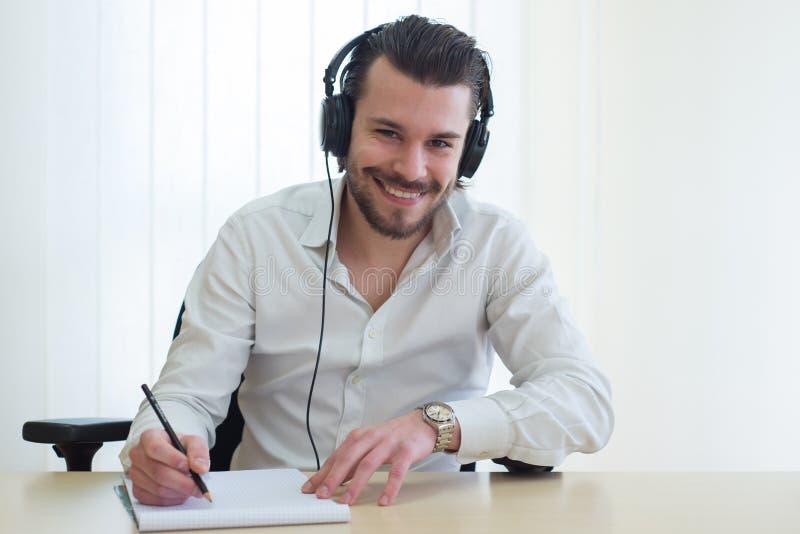 Бизнесмен который слушает к музыке с bonnets и он пишут стоковые изображения