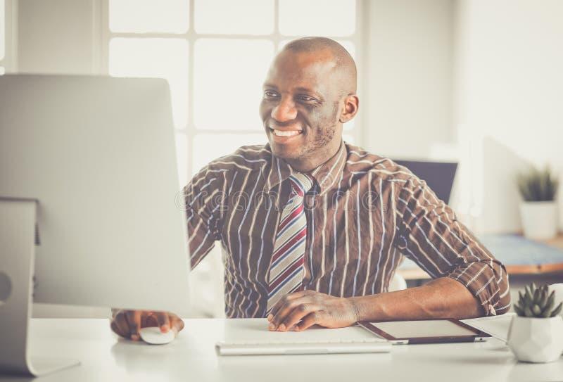 Бизнесмен красивого Афро американский в классическом костюме использует компьтер-книжку и усмехается пока работающ в офисе стоковое фото