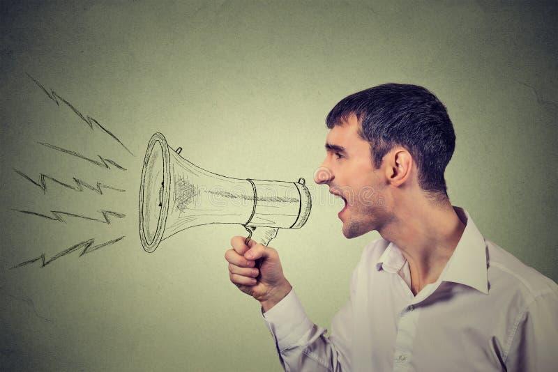 Бизнесмен крича в мегафон изолированный на серой предпосылке стоковые фотографии rf