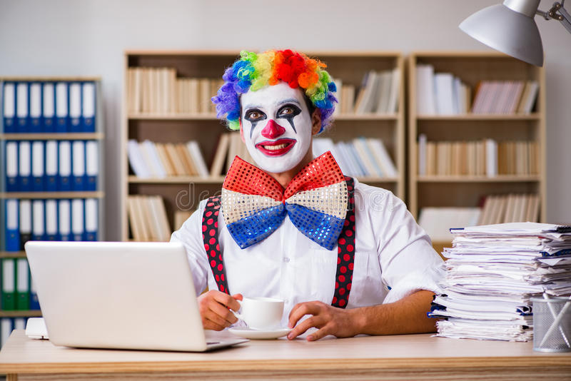 Бизнесмен клоуна работая в офисе стоковые фото