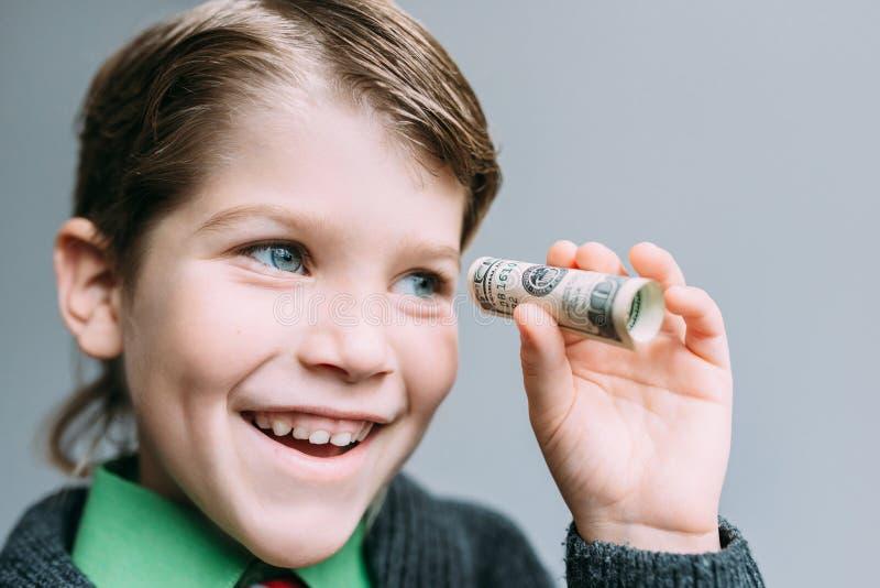 Бизнесмен мальчика смотрит через малую трубку от доллара стоковые фото
