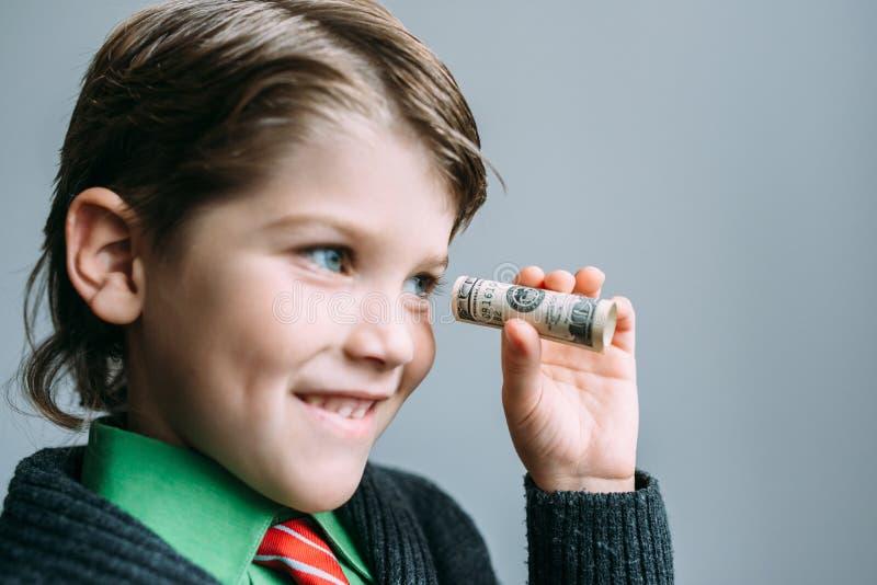 Бизнесмен мальчика смотрит через малую трубку от доллара стоковые фотографии rf