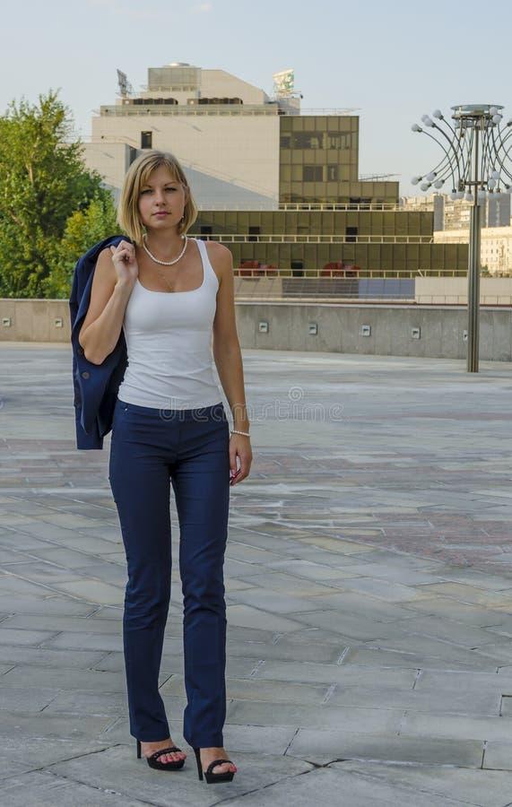 Бизнесмен молодой женщины идя после тяжелого дня на предпосылке делового центра стоковые фото