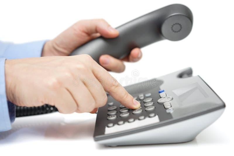 Бизнесмен набирает телефонный номер с телефонной трубкой в руке стоковое изображение rf