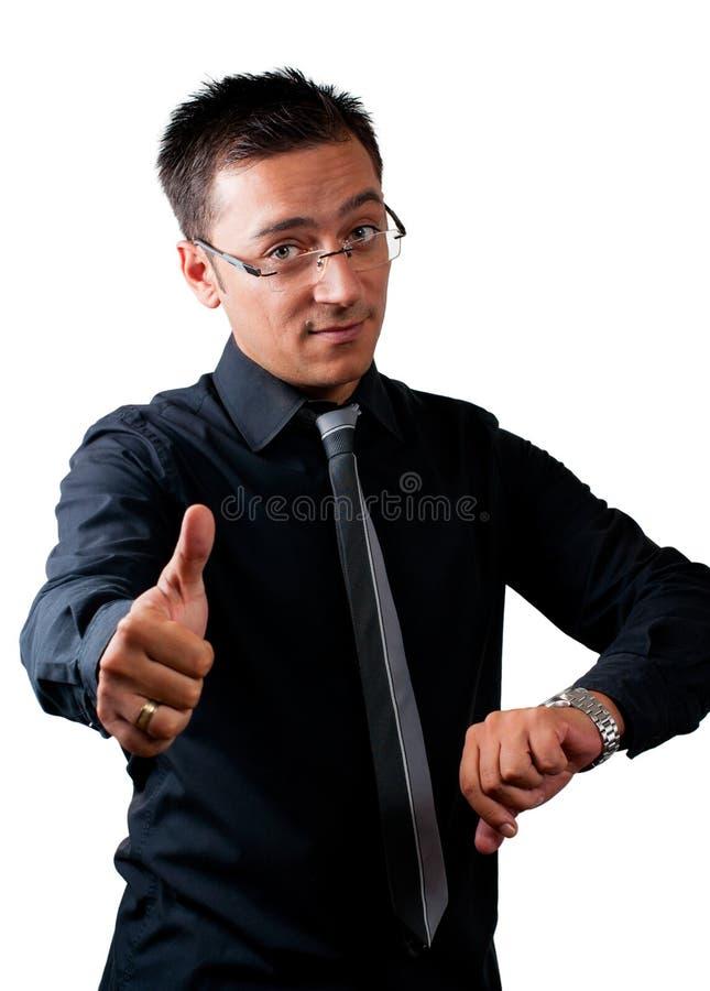 Бизнесмен наблюдая его вахту и показывая большой палец руки вверх стоковая фотография