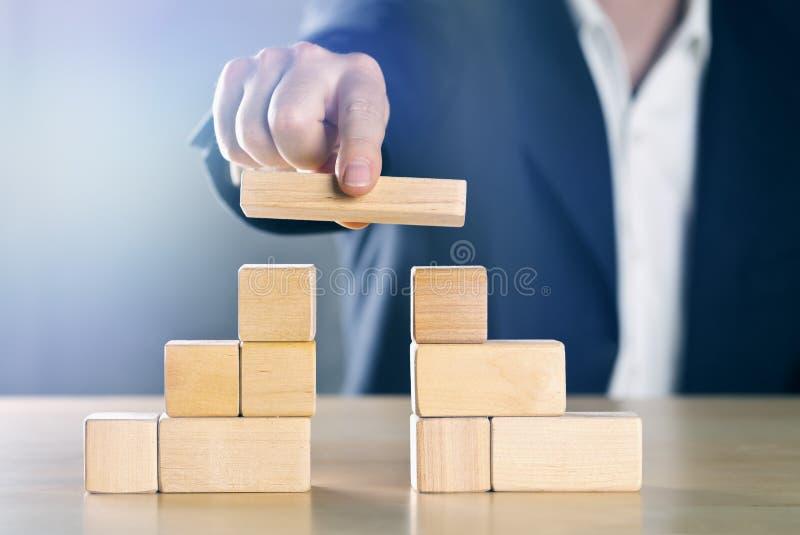 Бизнесмен наводя зазор между 2 башнями или партиями сделанными из деревянных блоков; управление конфликта или концепция посредник стоковое фото