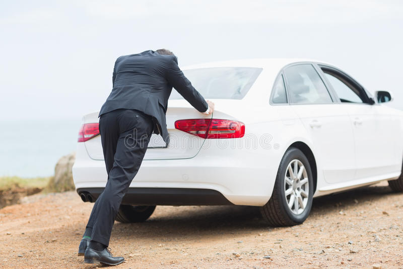 Бизнесмен нажимая его автомобиль стоковая фотография rf