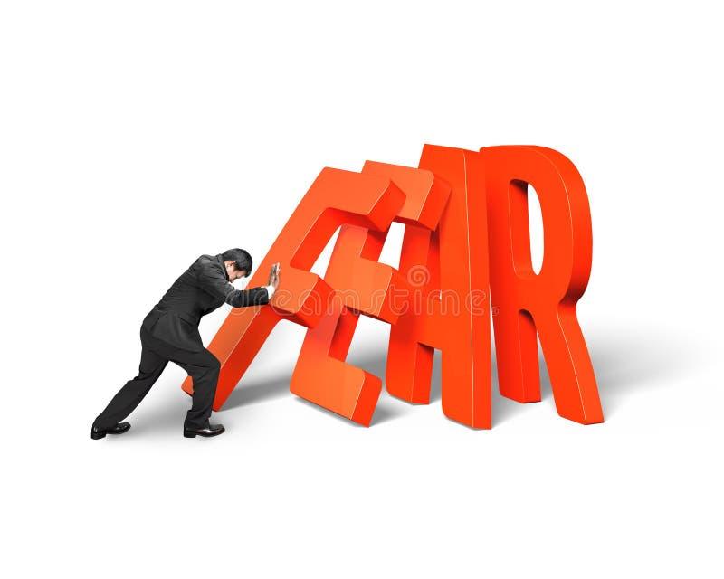 Бизнесмен нажимая домино красный падать слова страха стоковое изображение rf