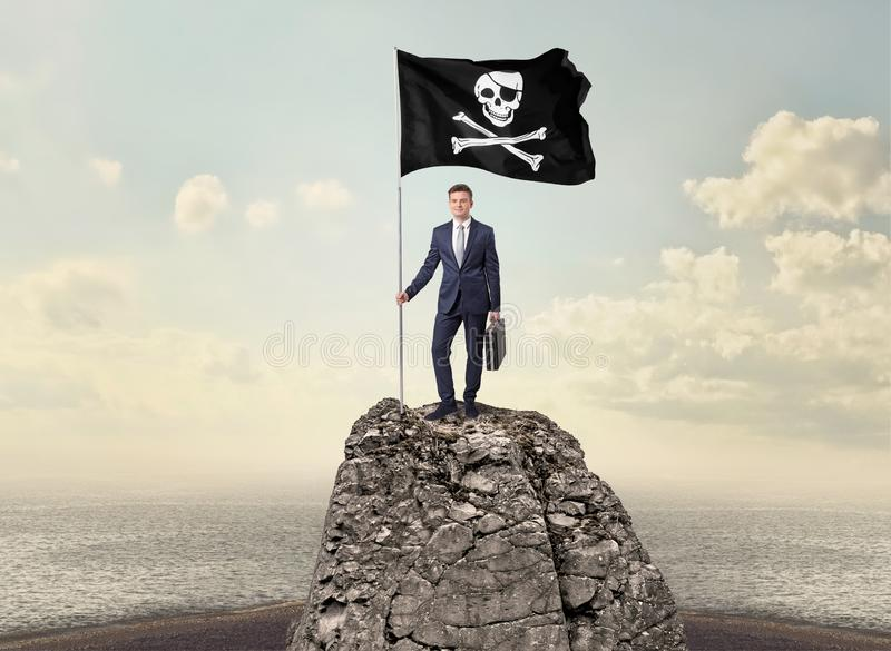 Бизнесмен на верхней части утеса держа флаг пирата стоковая фотография