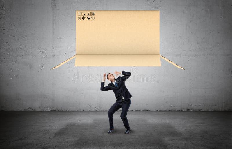 Бизнесмен на конкретной предпосылке сжимаясь под большой открытой коробкой коробки падая на его стоковое изображение rf