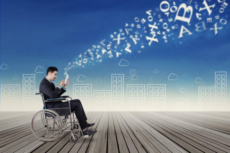 Бизнесмен на кресло-коляске посылая информацию стоковая фотография