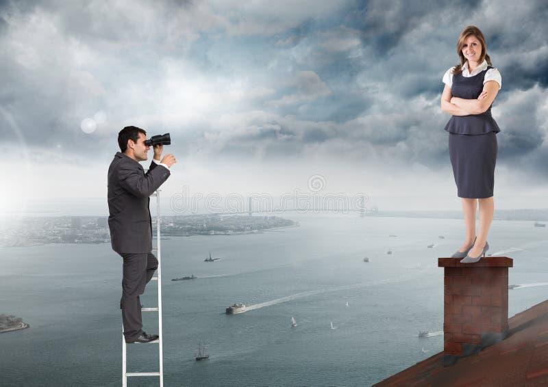 Бизнесмен на лестнице смотря коммерсантку стоя на крыше с печной трубой и пасмурным портом города стоковые изображения rf