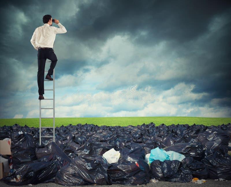 Бизнесмен на лестницы ищет далеко для чистой окружающей среды преодолевайте глобальную проблему загрязнения стоковое фото rf