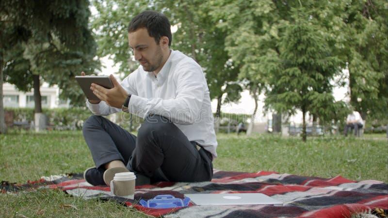 Бизнесмен на парке с таблеткой Молодой бизнесмен на парке работая с таблеткой стоковые фотографии rf