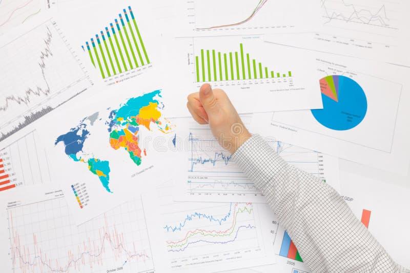 Бизнесмен на таблице при различные финансовые данные держа большой палец руки вверх стоковые изображения