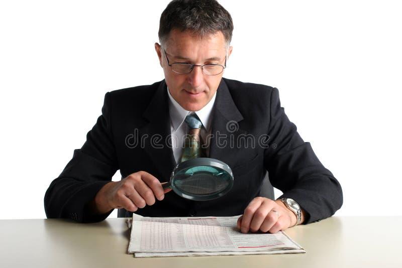 Бизнесмен на таблице проверяя его результаты стоковые фото