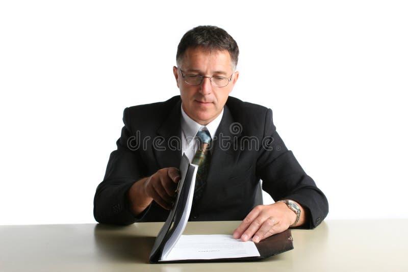 Бизнесмен на таблице проверяя его результаты стоковое фото rf